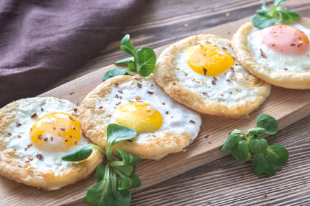 Baked eggs in puff pastry on the wooden board Foto de archivo - 95636098
