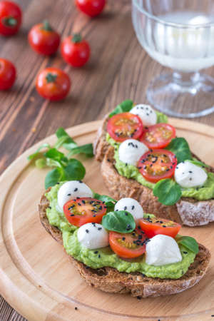 Sandwiches with avocado paste, cherry tomatoes and mozzarella