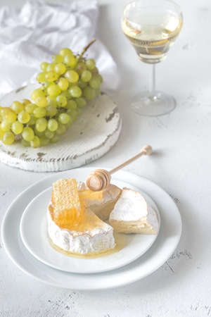 Camembert with honey, grapes and glass of white wine Reklamní fotografie - 112411330