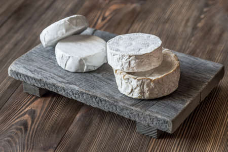 Heads of Camembert on the wooden board Stock Photo