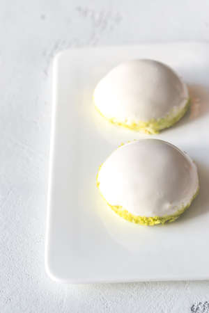 Sponge cakes in yogurt glaze with pistachio crumbles