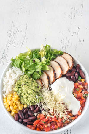 Burrito bowl with chicken, salsa, corn, rice, kidney beans and guacamole 免版税图像 - 115317434