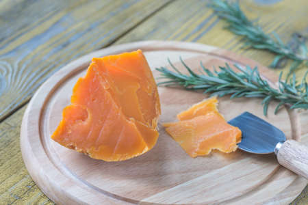 Wedge of Mimolette cheese on the wooden board Stock Photo