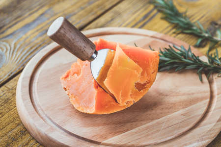 Wedge of Mimolette cheese on the wooden board 스톡 콘텐츠
