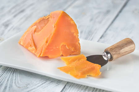 Wedge of Mimolette cheese on white plate