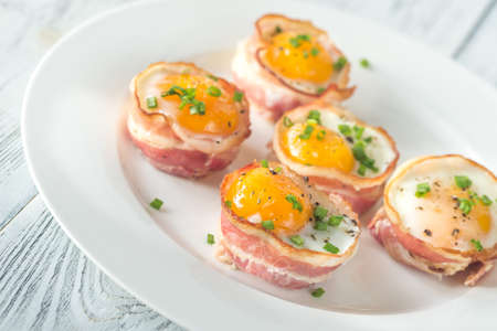 Bacon and egg cups on the white plate: top view