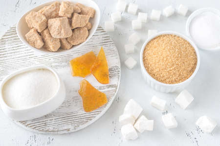 Different kinds of sugar on the wooden background