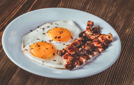 Fried eggs and bacon on the white plate on the wooden table Stock Photo