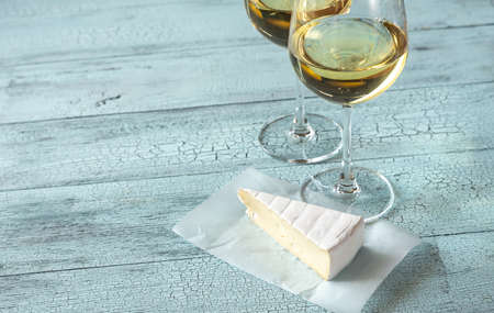 Two glasses of white wine with Brie on the wooden background