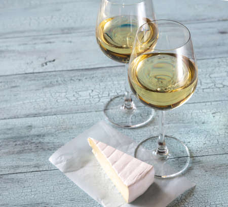 Two glasses of white wine with Brie on the wooden background Stock Photo