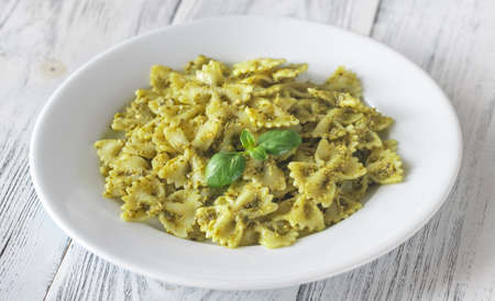 Portion of farfalle with pesto on the white wooden table 免版税图像