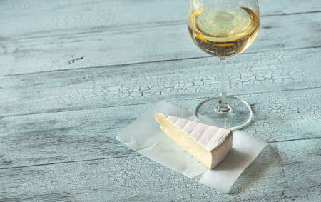Glass of white wine with Brie on the wooden
