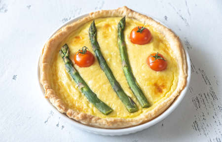 Open pie with asparagus and cherry tomatoes on the wooden table