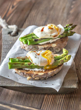 Sandwich with cream cheese, grilled asparagus and poached egg Imagens