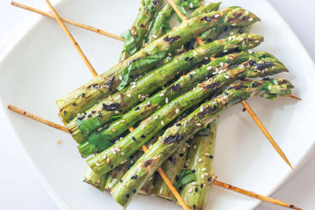 Grilled asparagus rafts with sesame seeds on the plate