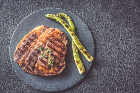 Grilled beef steak garnished with asparagus on the black stone board