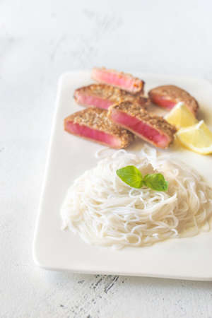 Rice noodles with fried tuna in sesame seeds on the white plate