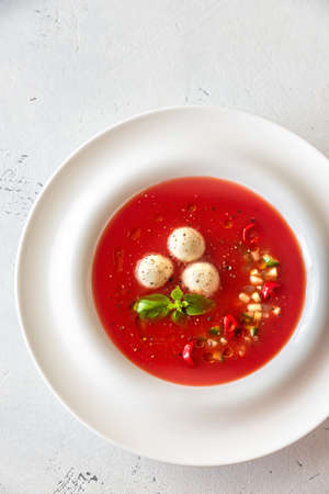 Portion of gazpacho with bocconcini on the wooden table Stock Photo