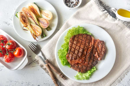 Grilled beef steak garnished with fresh lettuce, onions and cherry tomatoes