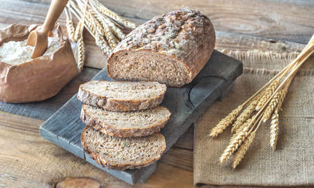 Wholegrain bread with ears of wheat on the wooden board