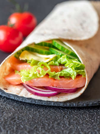 Tortilla wrap with salmon, cheese and vegetables on the stone board
