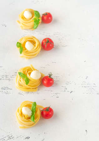 Raw fettuccine with mozzarella balls, cherry tomatoes and fresh basil leaves on the white background Stock Photo