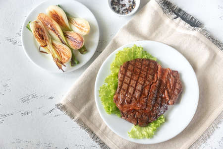 Grilled beef steak garnished with fresh lettuce and onions Stock Photo