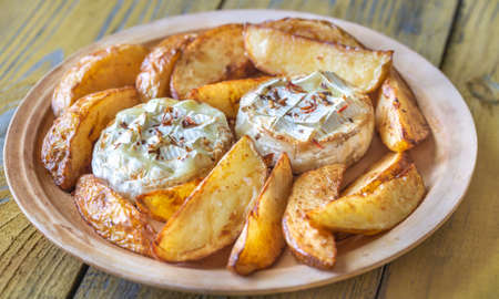 Baked Camembert cheese with roasted potatoes on the plate Imagens