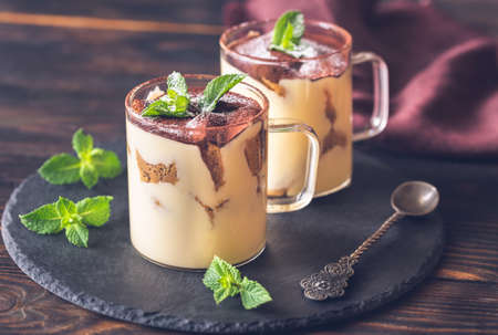 Two glass mugs of tiramisu decorated with cocoa and fresh mint leaves