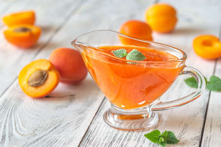Glass vase of apricot jam with fresh apricots on the wooden background Stock Photo