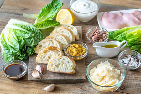 Ingredients for Caesar salad on the wooden background