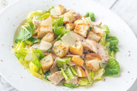 Portion of Caesar salad on the wooden table Stock Photo