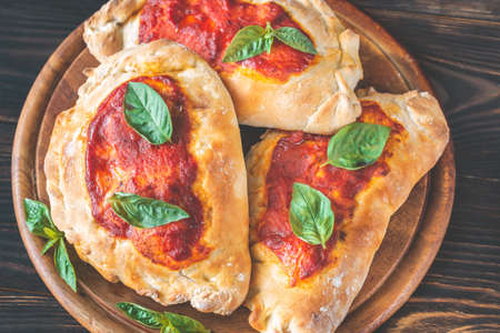 Homemade calzone stuffed with pancetta and mushrooms on the wooden board Stock Photo