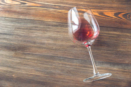 Glass of red wine laying on the wooden background