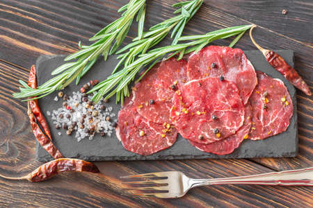 Carpaccio - slices of raw beef on the stone board