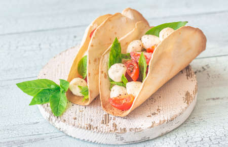 Caprese tacos on the wooden board Stock Photo