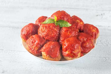 Bowl of meatballs with tomato sauce and fresh basil