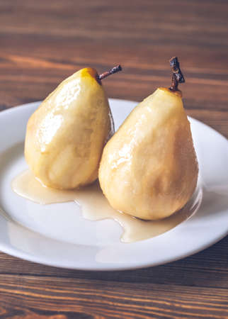 Poached pears in white wine on the white plate