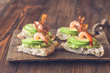Sandwiches with guacamole, sliced avocado and shrimps on the wooden board