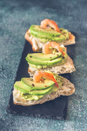 Sandwiches with guacamole, sliced avocado and shrimps
