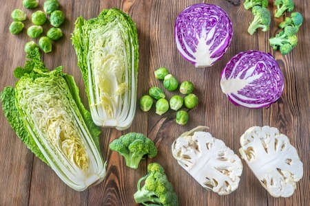 Assortment of different Cruciferous vegetables on the wooden background Imagens