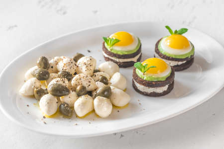 Appetizer with canape, mozzarella and capers on the white plate