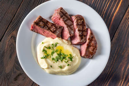 Slices of strip steak with celery puree