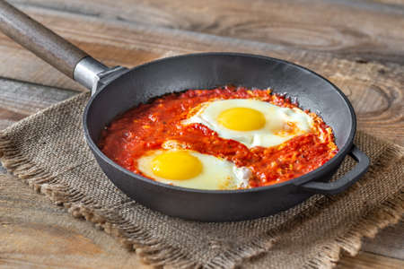 Shakshouka - eggs poached in tomato sauce, served in frying a pan Standard-Bild - 133908488