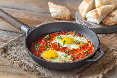 Shakshouka - eggs poached in tomato sauce, served in a frying pan Standard-Bild - 133908489