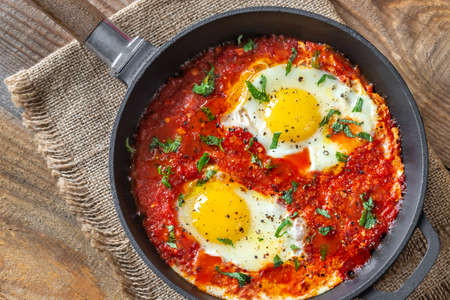 Shakshouka - eggs poached in tomato sauce, served in a frying pan Standard-Bild - 133908490