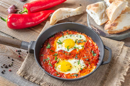 Shakshouka - eggs poached in tomato sauce, served in a frying pan Standard-Bild - 133908491