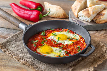 Shakshouka - eggs poached in tomato sauce, served in a frying pan