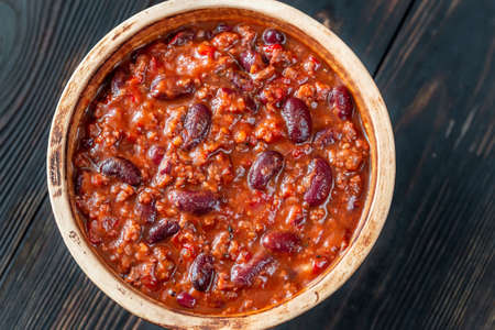 Bowl of chili con carne on a wooden table: top view