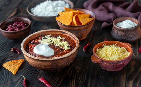 Bowl of chili con carne with toppings on a wooden table Stockfoto